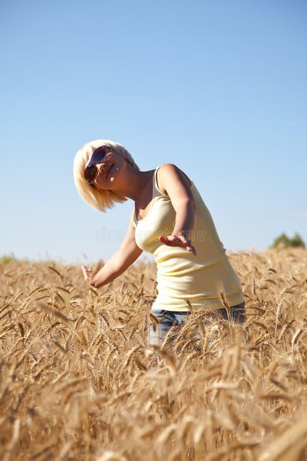 Mulher nova no campo de trigo fotografia de stock
