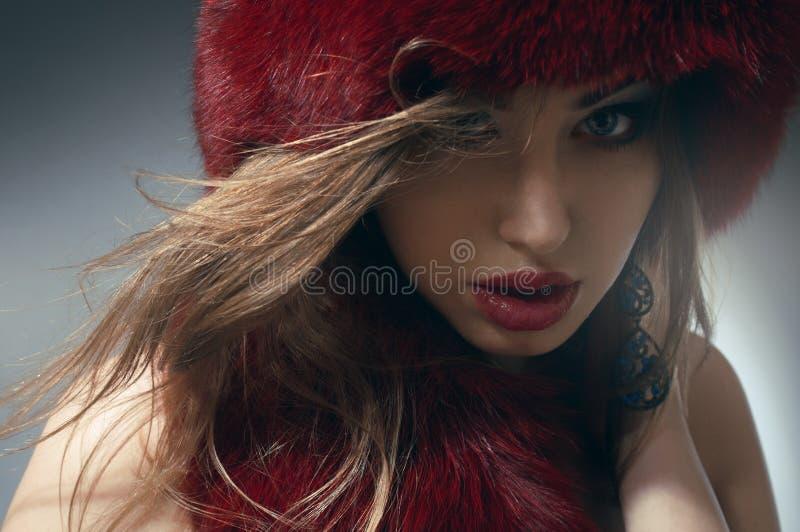 Mulher nova no chapéu forrado a pele vermelho fotografia de stock