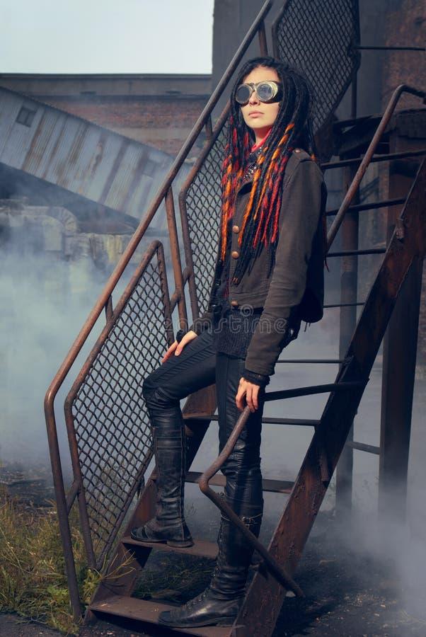 Mulher nova no estilo industrial que está em escadas fotografia de stock royalty free