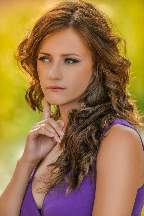 Mulher nova no pensamento roxo do vestido fotografia de stock royalty free