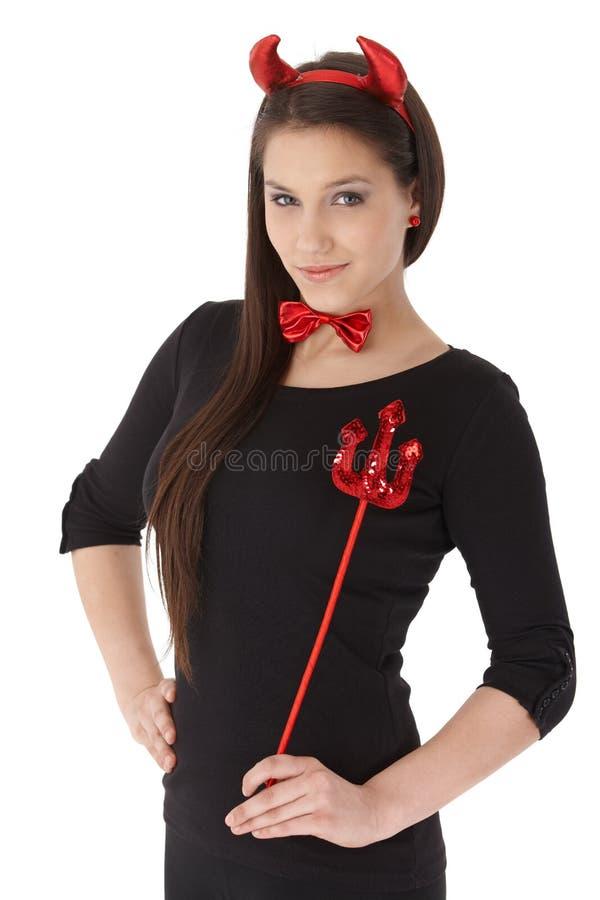 Mulher nova no sorriso do traje do diabo imagem de stock royalty free