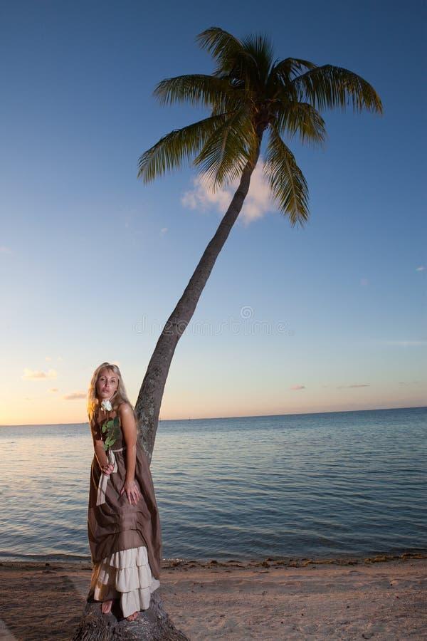 A mulher nova no sundress longos em uma praia tropical polynesia foto de stock