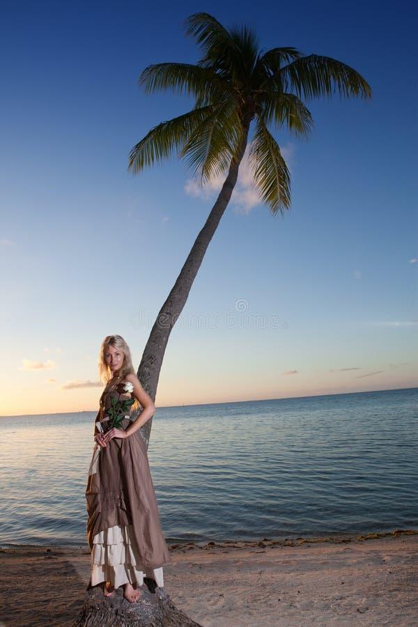 A mulher nova no sundress longos em uma praia tropical polynesia imagens de stock
