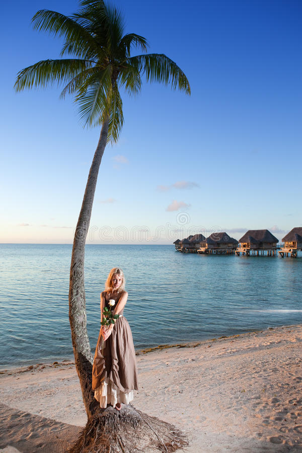 A mulher nova no sundress longos em uma praia tropical polynesia fotografia de stock