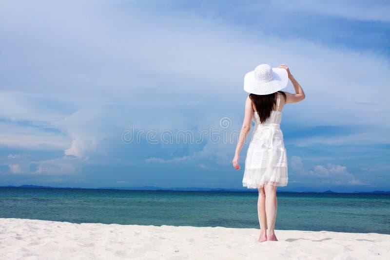 Mulher nova no vestido branco na praia fotografia de stock