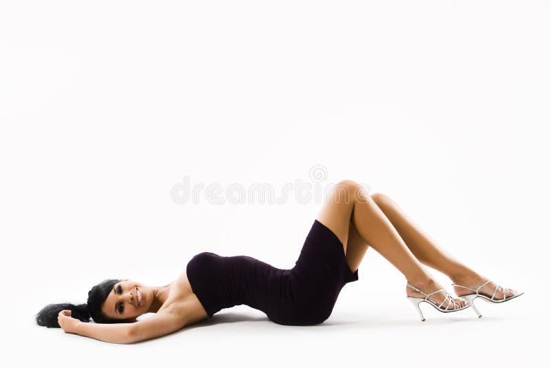 Mulher nova no vestido 'sexy' que encontra-se sobre para trás foto de stock royalty free