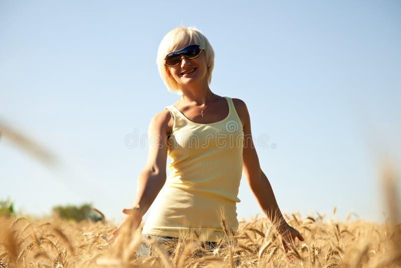 Mulher nova nos óculos de sol no campo de trigo fotografia de stock royalty free