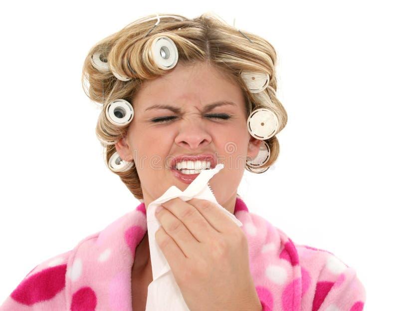 Mulher nova nos rolos e na veste que Sneezing fotos de stock royalty free