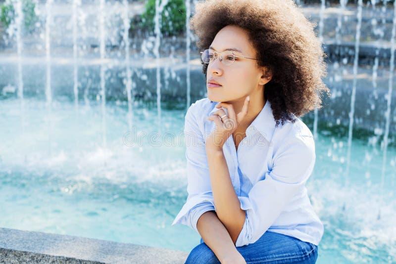 Mulher nova pensativa bonita da raça misturada com vidros fotos de stock royalty free