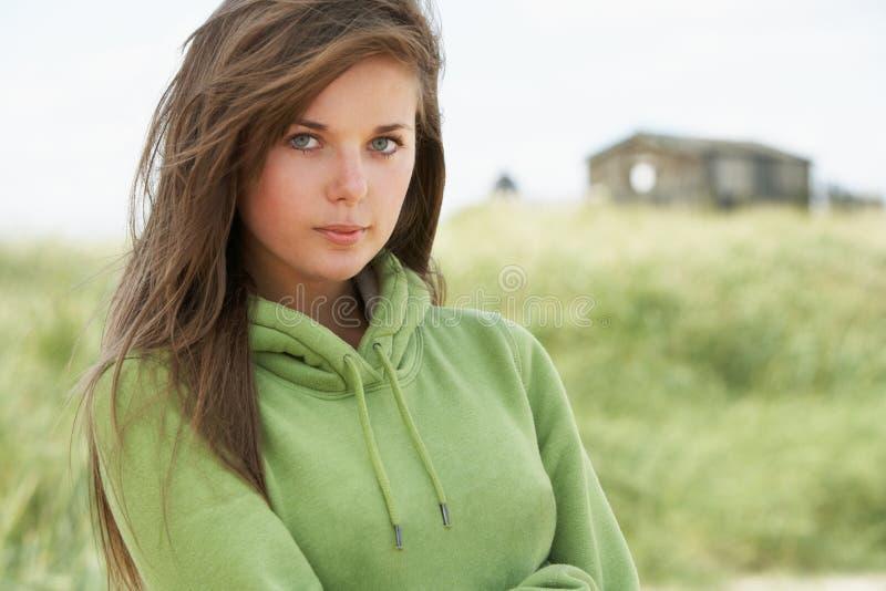 Mulher nova pensativa que está na praia imagens de stock