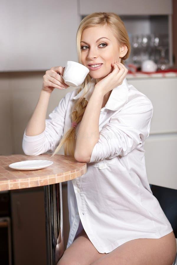 A mulher nova prende um copo do coffe imagem de stock royalty free