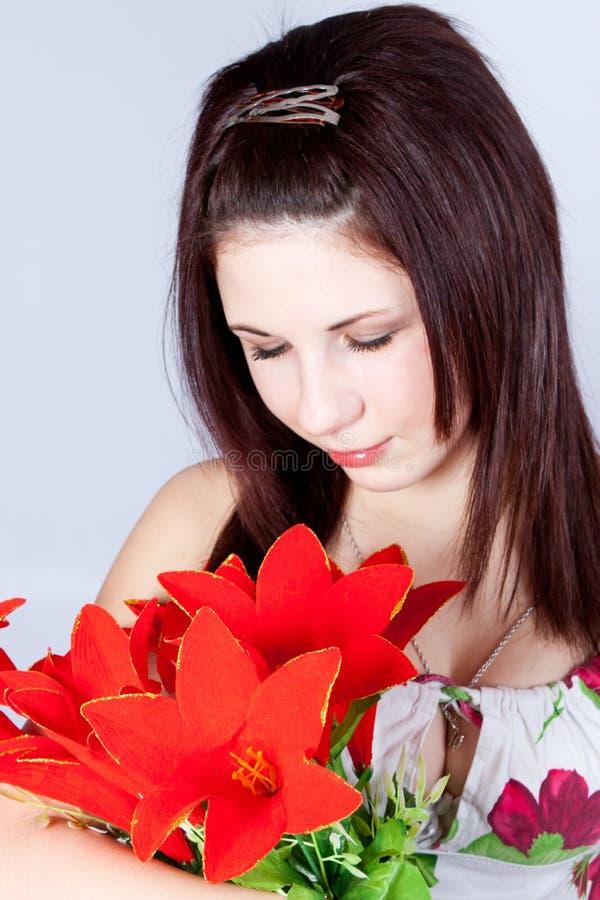 Mulher nova que abraça flores fotografia de stock royalty free