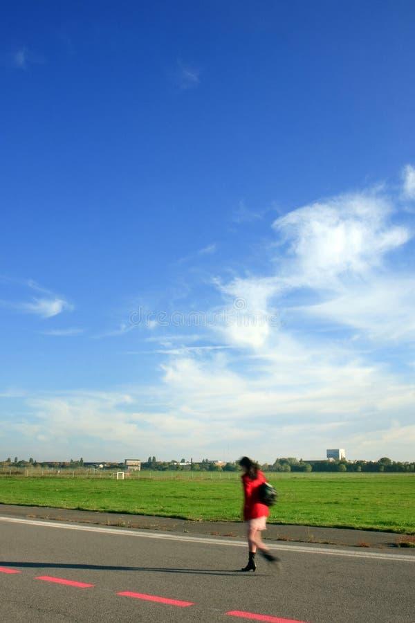 Mulher nova que anda ao longo de uma pista de decolagem fotografia de stock royalty free