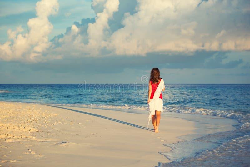 Mulher nova que anda na praia fotos de stock royalty free