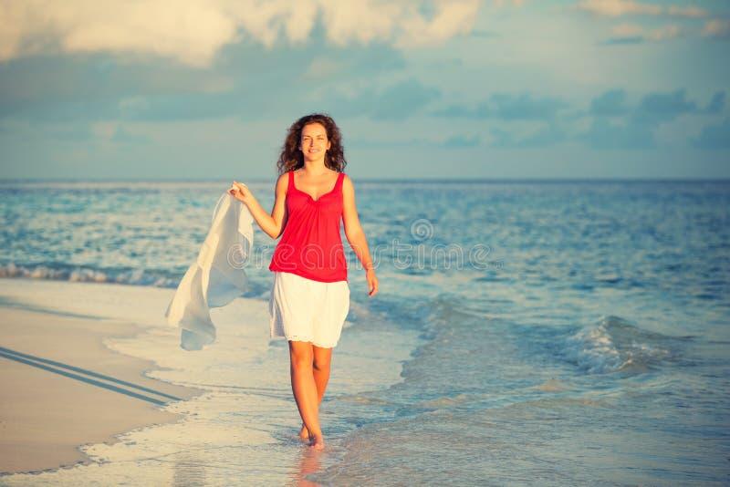 Mulher nova que anda na praia fotografia de stock