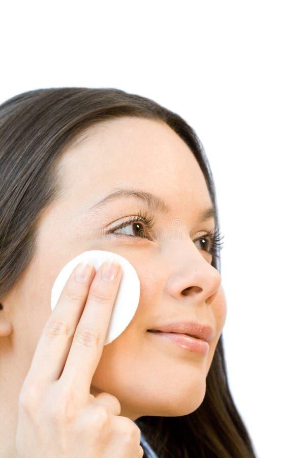 Mulher nova que aplica almofadas de algodão da face foto de stock
