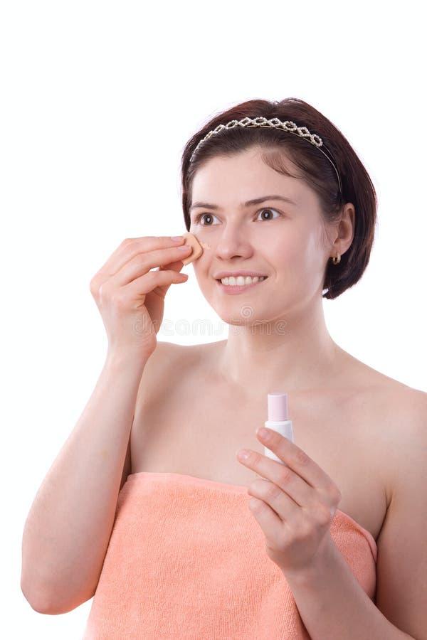 Mulher nova que aplica a nata do tonalizador na face imagem de stock