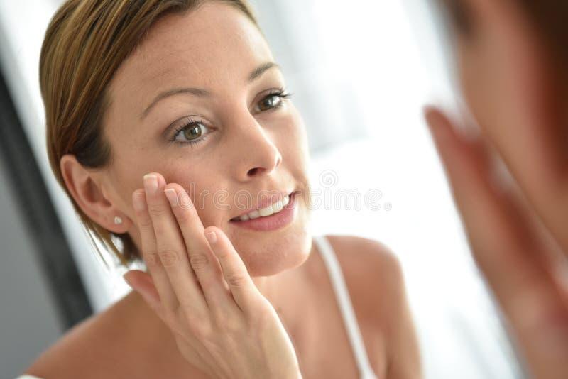 Mulher nova que aplica o creme facial fotografia de stock