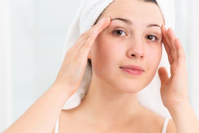 Mulher nova que aplica o creme facial fotografia de stock royalty free