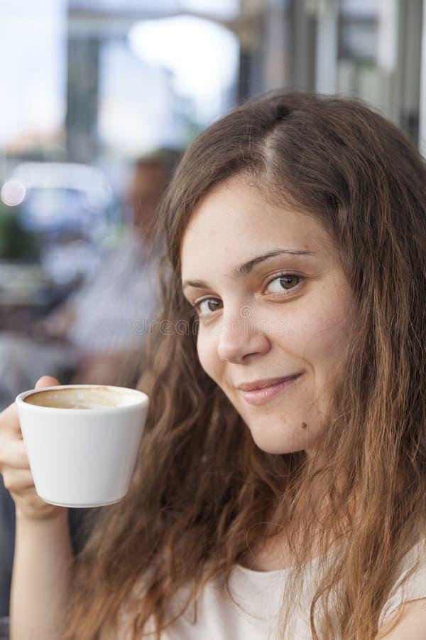 Mulher nova que aprecia o café fotografia de stock royalty free