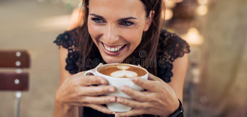 Mulher nova que aprecia uma chávena de café imagem de stock