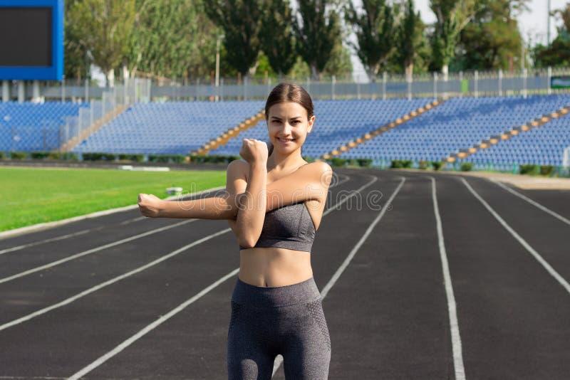 A mulher nova que aquece-se, menina da aptidão dos esportes tem o esticão do treinamento no estádio de corrida Os povos ostentam  imagens de stock royalty free