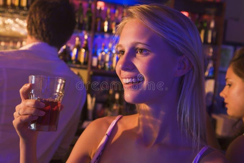 Mulher nova que bebe em um clube nocturno fotos de stock royalty free
