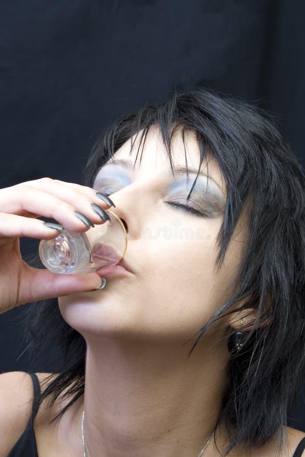 Mulher nova que bebe um tiro foto de stock royalty free