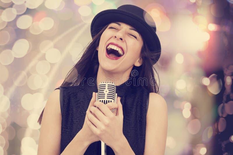 Mulher nova que canta com o microfone imagem de stock