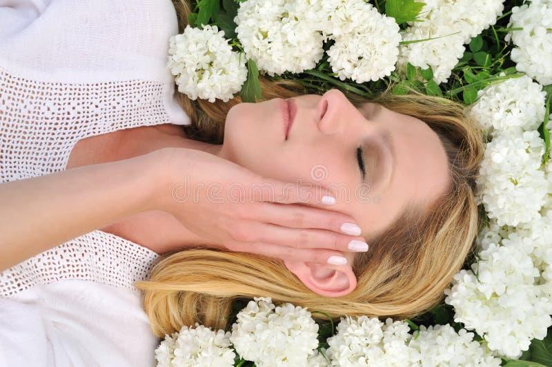 Mulher nova que coloca nas flores - snowballs foto de stock