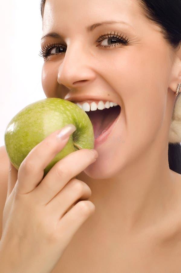 Mulher nova que come a maçã imagem de stock