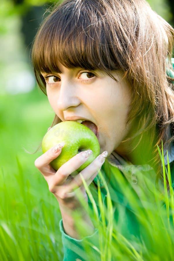 Mulher nova que come a maçã verde fotos de stock royalty free
