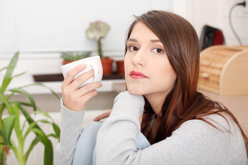 Mulher nova que come o café ou o chá na cozinha imagem de stock