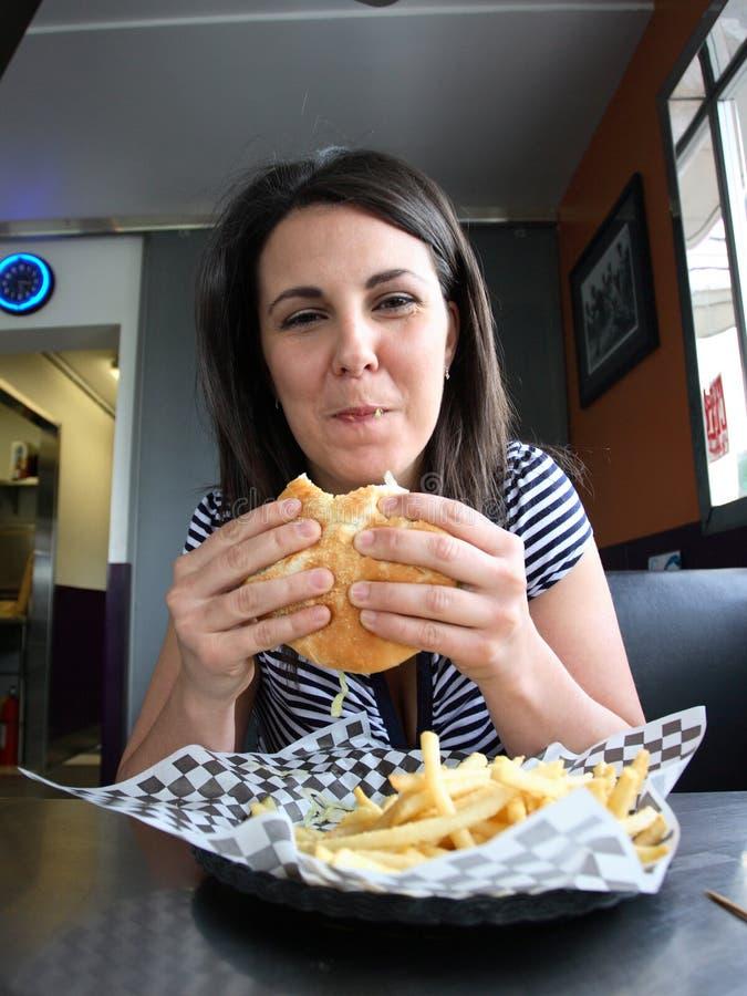 Mulher nova que come o Hamburger fotografia de stock royalty free