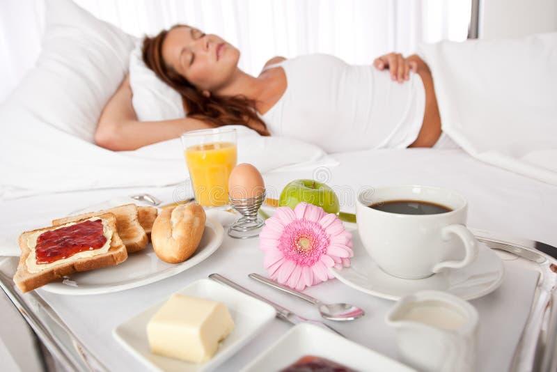 Mulher nova que come o pequeno almoço na cama fotografia de stock royalty free