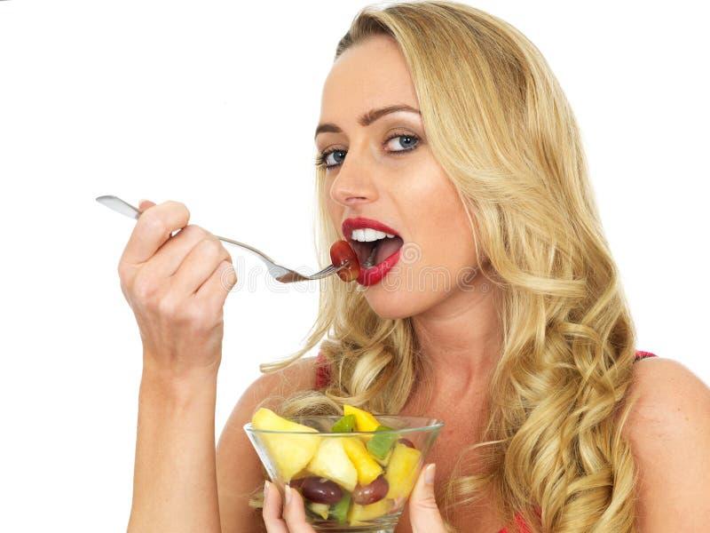 Mulher nova que come a salada da fruta fresca foto de stock royalty free