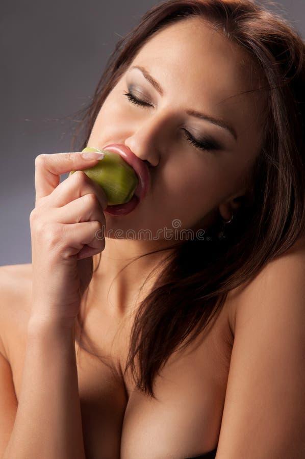 Mulher nova que come uma fruta de quivi imagens de stock royalty free
