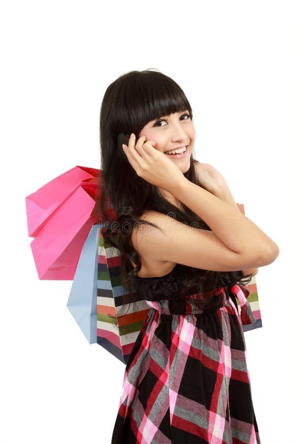Mulher nova que compra e que chama seus amigos foto de stock