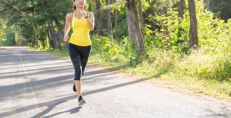 Mulher nova que corre na estrada na manhã, corredor novo do esporte da aptidão do desportista da aptidão que corre na fuga tropic foto de stock