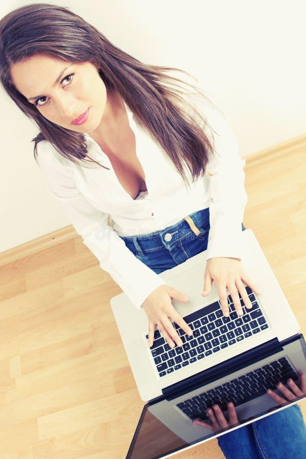 Mulher nova que datilografa no computador portátil imagens de stock royalty free
