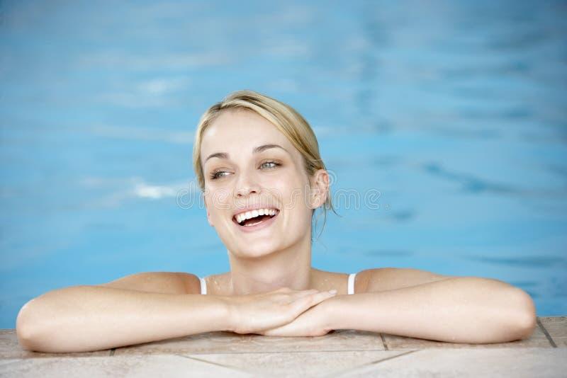 Mulher nova que descansa na borda da piscina foto de stock