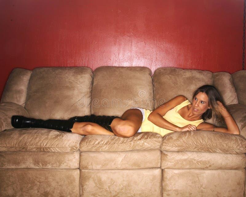 Mulher nova que descansa no sofá fotografia de stock