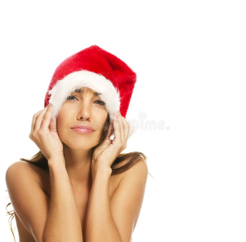 Mulher nova que desgasta o chapéu de Santa que faz as faces imagem de stock royalty free