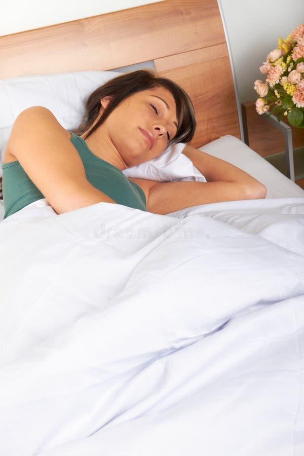 Mulher nova que dorme na cama fotos de stock royalty free
