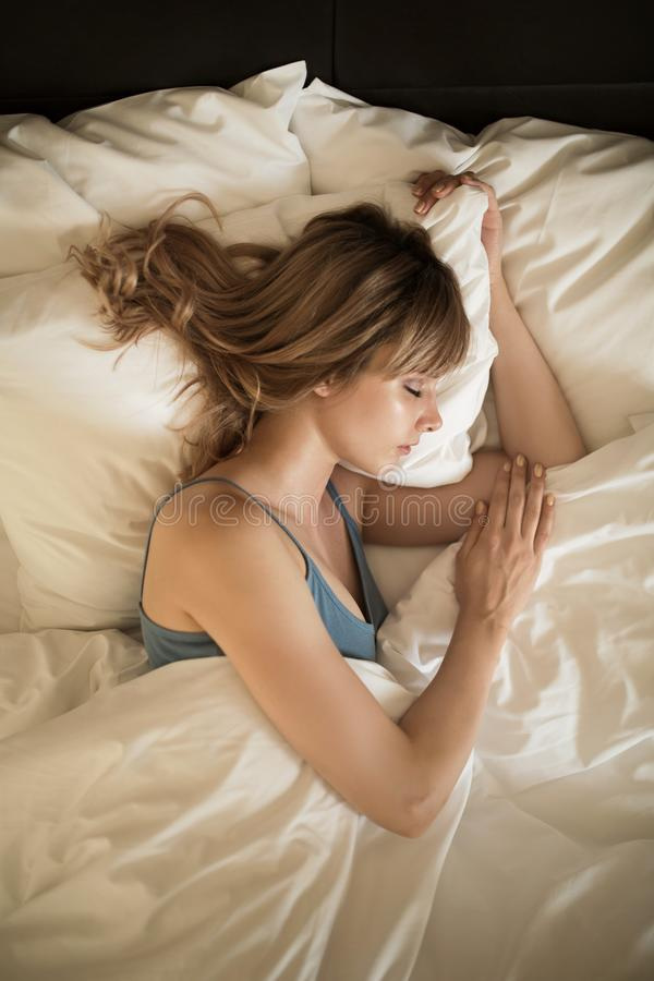 Mulher nova que dorme na cama Manhã foto de stock