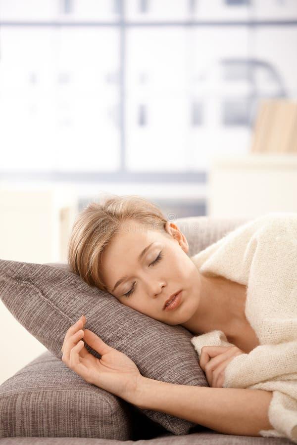 Mulher nova que dorme no sofá imagens de stock royalty free