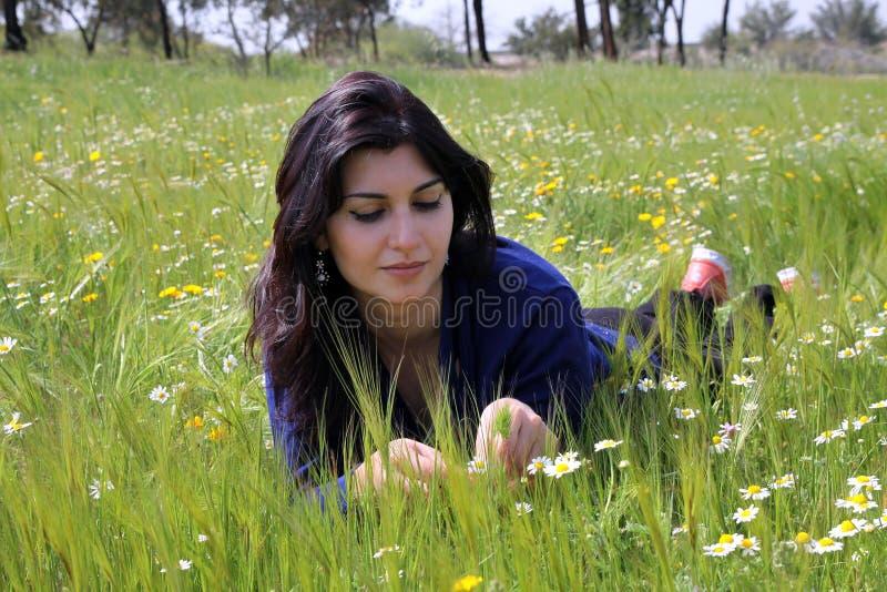 Mulher nova que encontra-se em um prado foto de stock royalty free