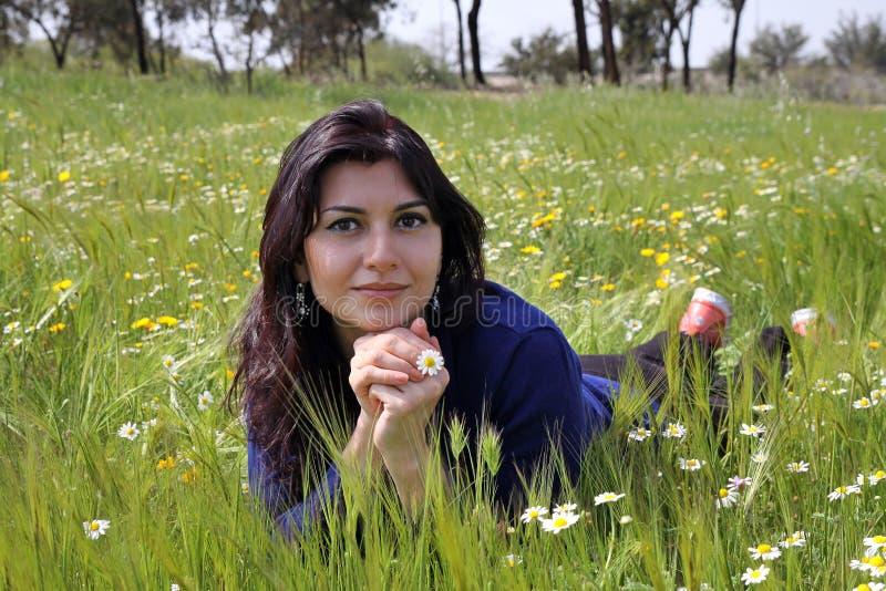 Mulher nova que encontra-se em um prado imagem de stock royalty free