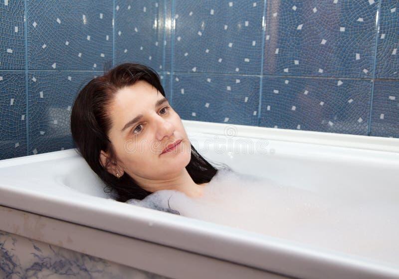 Mulher nova que encontra-se em uma banheira