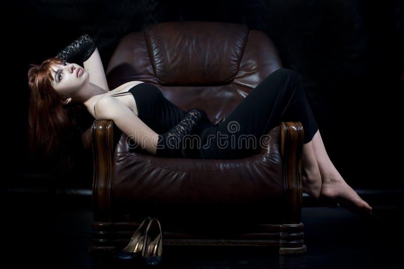 Mulher nova que encontra-se na cadeira de couro fotografia de stock royalty free